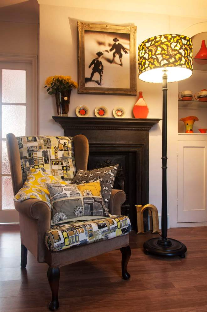 I recovered this old wing-back chair I found online in some gorgeous 1950s barkcloth and some donkey-brown velvet. I've teamed this with a couple of contemporary print cushions and a cushion I made myself with Lucienne Day-style prints. This colour scheme is predominantly grey, black, and yellow, but I've lifted it with the lampshade, which has orange, green and blues in the pattern, and with the orange accent ceramic pieces.