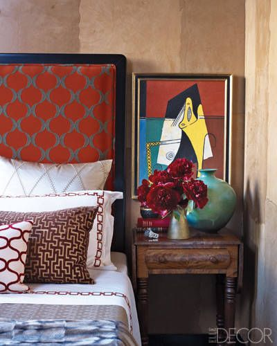 A bedside table can double up as a tiny 'gallery' space. (elledecor.com)